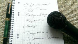 Zettel mit Notizen zur Moderation, sowie ein Füller und ein Mikrofon