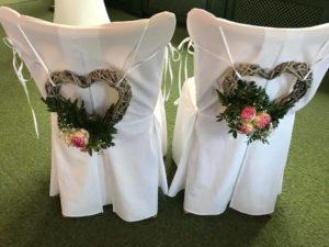 Zwei Stühle mit weißen Hussen und Blumenschmuck