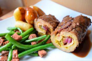 Foto eines Tellers mit Essen, Kartoffeln, grüne Bohnen, vegane Rouladen